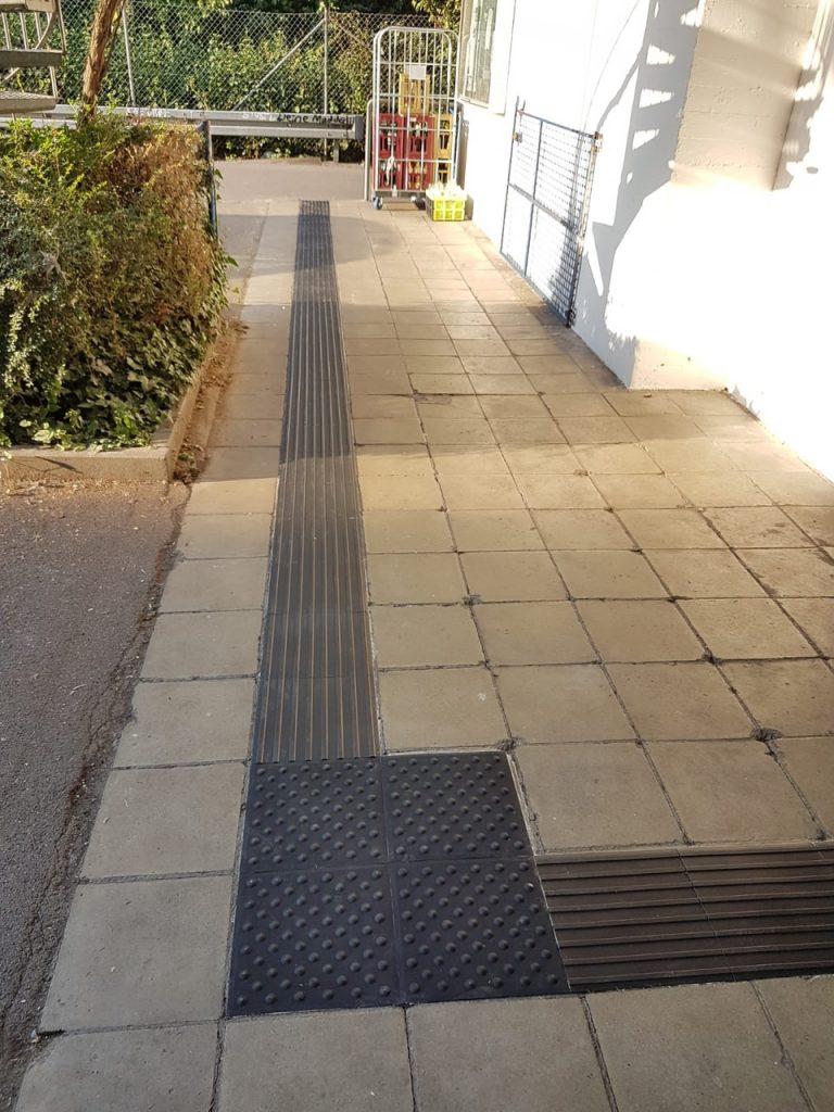 Hier die Blindenleitlinie von der Straße bis zum Eingang ins Bootshaus